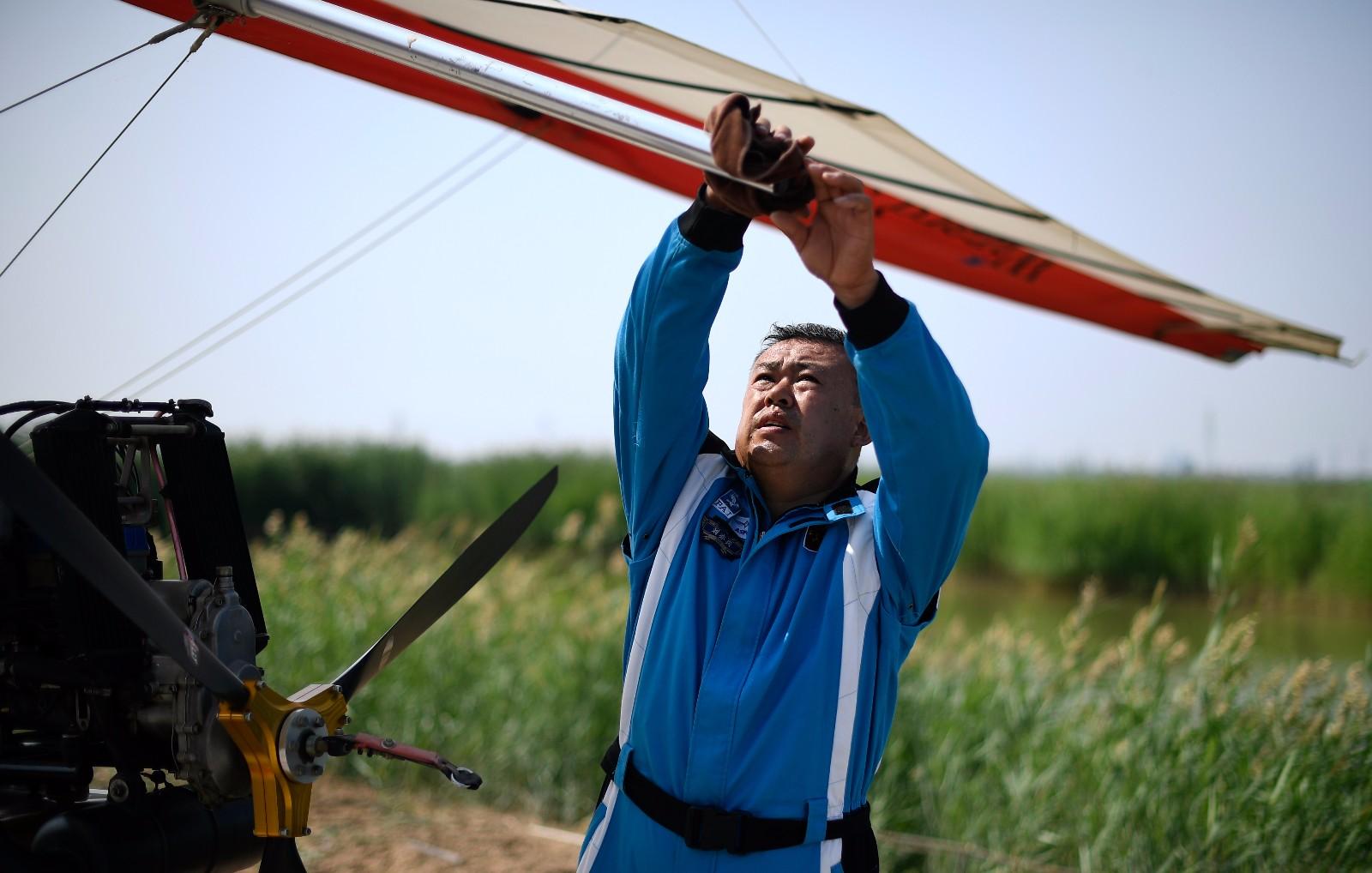 刘亦兵在飞行前对动力三角翼飞机进行检查(6月21日摄)。