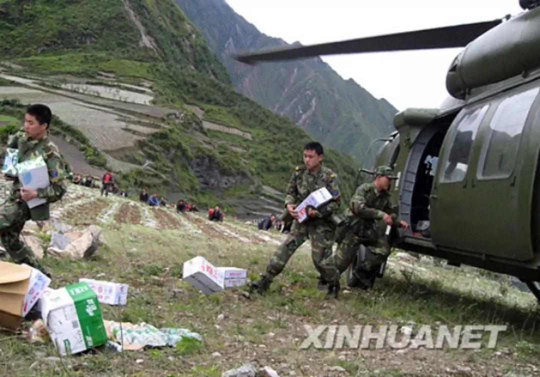 2008年5月14日,乘坐直升機抵達汶川的解放軍在搬運救援物資。 新華社記者徐壯志攝